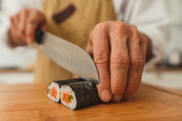 L'uomo dei sushi fa il cuoco unico asiatico grandangolare dell'uomo dei rotoli di sushi nella fetta uniforme finito il rotolo in pezzi