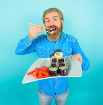 Uomo di sushi con sushi in bacchette giappone hipster che mangia sushi sushi consegna cibo giapponese sottaceto