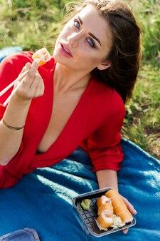 Sushi vicino alle labbra della ragazza con gli occhi azzurri al picnic. consegna del cibo dal ristorante giapponese. annuncio fotografico verticale per i social network. la ragazza graziosa mangia il set di sushi nel parco.