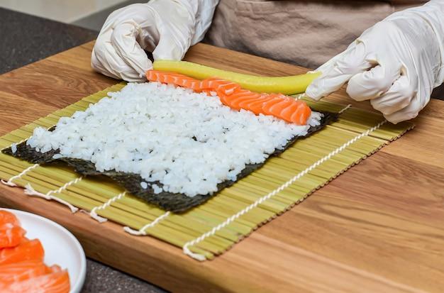 Processo di preparazione del sushi. le mani delle donne in guanti di gomma avvolgono i rotoli per sushi, sushi a casa