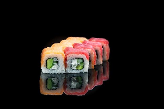 Rotolo di sushi su uno sfondo nero riflessione cibo giapponese da vicino