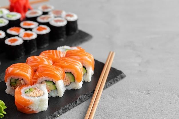 Rotolo di sushi ricoperto di salmone fresco servito sulla fine del piatto