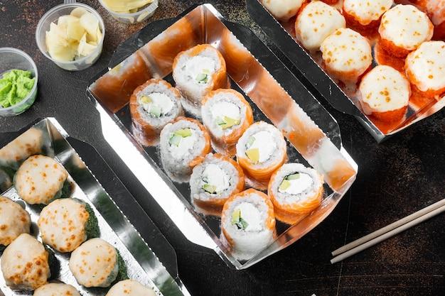Set di consegna di rotoli di sushi, su un vecchio tavolo rustico scuro