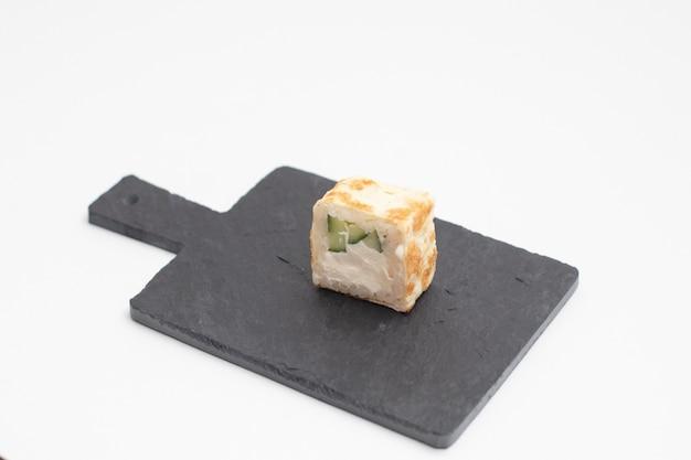 Rotolo di sushi in una frittella di uova su una tavola di ardesia nera.