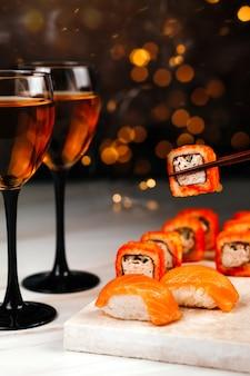 Rotolo di sushi su un tavolo festivo di capodanno su una tavola di marmo. sulla sinistra ci sono due bicchieri di vino. bellissimo bokeh sullo sfondo.