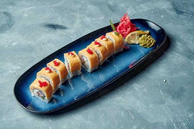 Rotolo di sushi drago d'oro con gamberetti, formaggio e caviale tobiko.