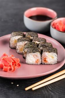 Rotolo di sushi in alga nori con caviale e crema di formaggio su una superficie scura