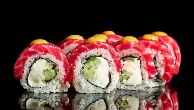 Rotolo di sushi philadelphia con salmone gravlax su sfondo nero. primo piano, messa a fuoco selettiva