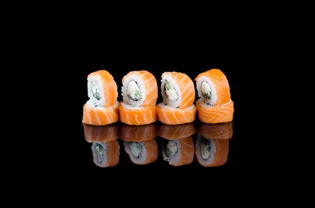 Rotolo di sushi philadelphia con salmone su sfondo nero