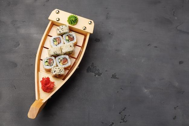 Rotolo di sushi servito sul piatto di barca di legno sulla vista superiore del fondo nero