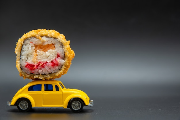Rotolo di sushi in cima a una macchinina gialla