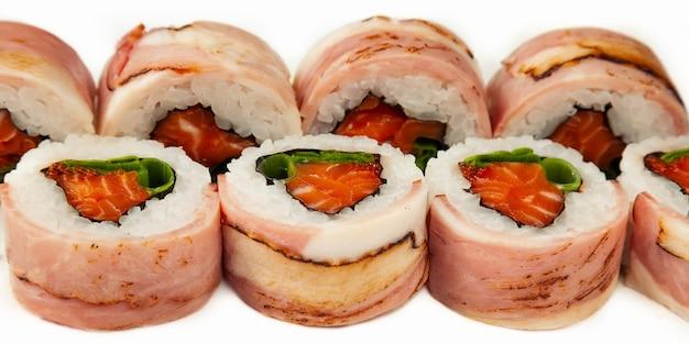 Rotolo di sushi con pancetta e salmone su uno sfondo bianco