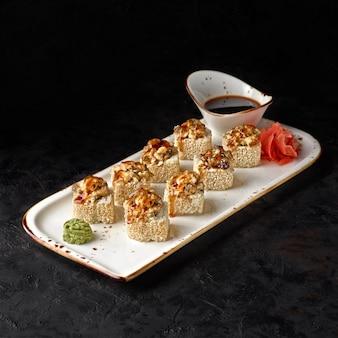 Rotolo di sushi con anguilla al forno da lastra di ardesia nera. avvicinamento