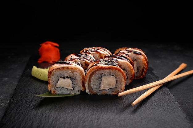 Rotolo di sushi con anguilla e crema di formaggio, su ardesia nera, su sfondo nero