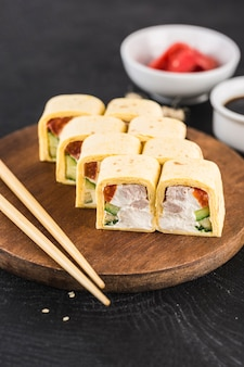 Rotolo di sushi con frittata di uova, pollo, cetriolo, paprika e crema di formaggio su una superficie scura