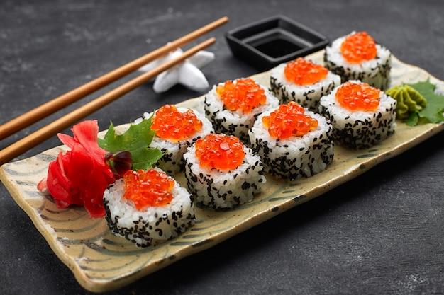 Rotolo di sushi con caviale rosso su un piatto con wasabi, zenzero, foglie di acero e bacchette per sushi, su sfondo nero