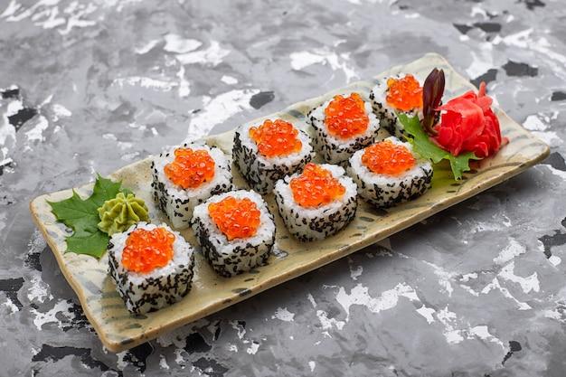 Rotolo di sushi con caviale rosso su un piatto con wasabi, zenzero, foglie di acero e bacchette per sushi, su uno sfondo chiaro