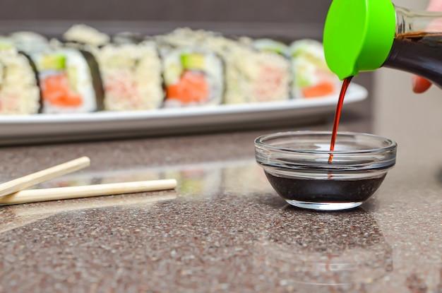 Rotolo di sushi con salmone e avocado. bella macro, profondità di campo ridotta, panini non affettati in un piatto, salsa di soia.