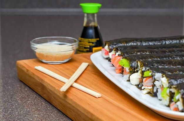 Rotolo di sushi con salmone e avocado. bella macro, profondità di campo ridotta, rotoli non affettati in un piatto