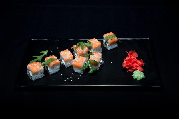 Rotolo di sushi con salmone e avocado sulla piastra su sfondo nero vista dall'alto