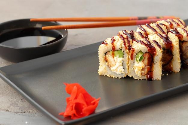 Rotolo di sushi con sesamo sulla fine del piatto in ceramica nera su
