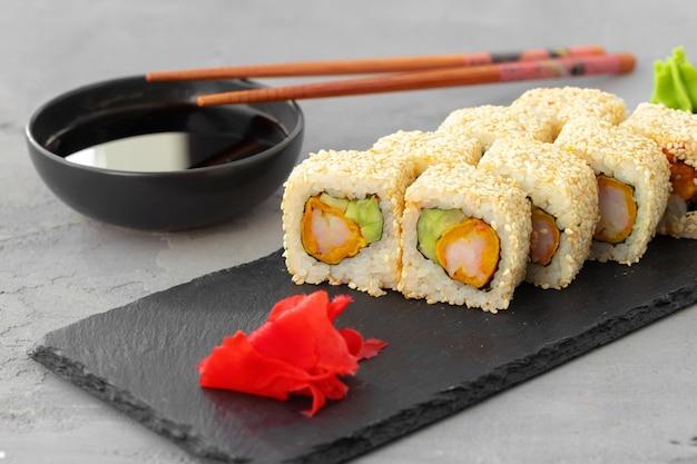 Rotolo di sushi con sesamo sul piatto in ceramica nera