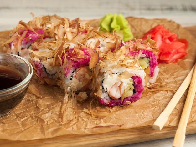 Rotolo di sushi con gamberetti, crema di formaggio e scaglie di anguilla.