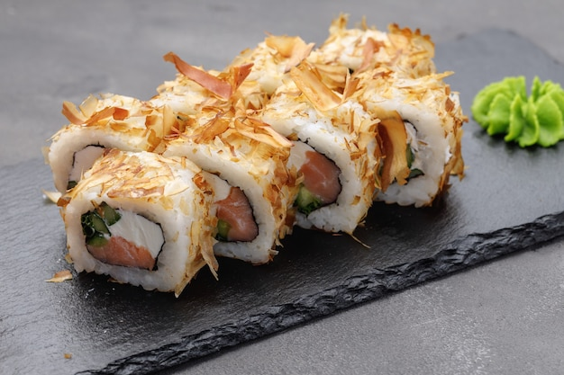 Rotolo di sushi con trucioli di tonno sulla fine del piatto sulla foto