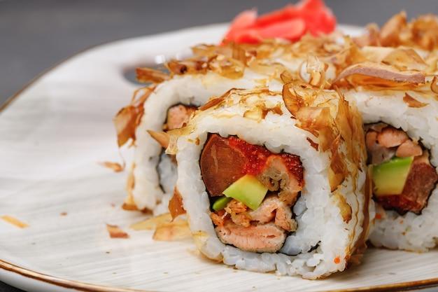 Rotolo di sushi con scaglie di tonno sulla piastra