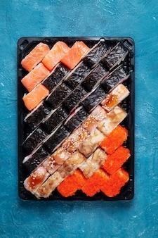 Rotoli di sushi su uno sfondo di pietra blu con bastoncini di bambù e salsa di soia
