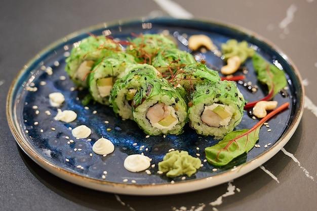 Rotoli di sushi su un piatto di ceramica con salsa, anacardi e wasabi su un tavolo di marmo nero