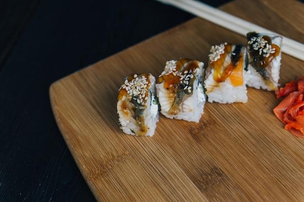 Rotoli di sushi bacchette cibo giapponese tavola di legno.