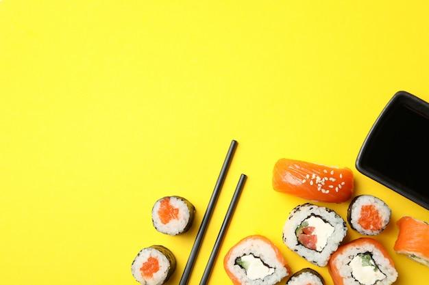 Rotoli di sushi, bacchette e soia sulla superficie gialla