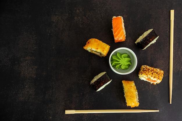 Rotoli di sushi su uno sfondo scuro a forma di fiore con wasabi, con un posto per il testo