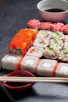 Sushi rotoli su uno sfondo di pietra scura con bastoncini di bambù e salsa di soia