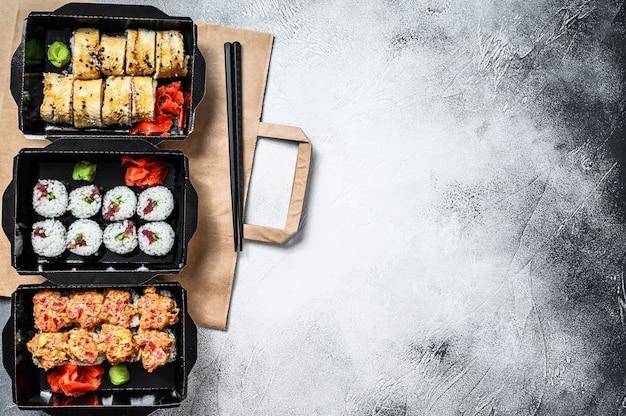 I rotoli di sushi nel pacchetto di consegna, ordinati nel ristorante sushi da asporto. vista dall'alto. copia spazio.