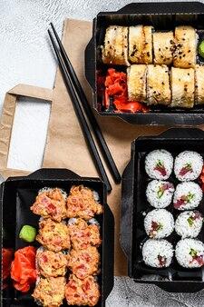 I rotoli di sushi nel pacchetto di consegna, ordinati nel ristorante sushi da asporto. vista dall'alto.