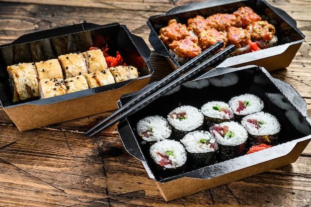 I rotoli di sushi nel pacchetto di consegna, ordinati nel ristorante sushi da asporto. superficie in legno. vista dall'alto.