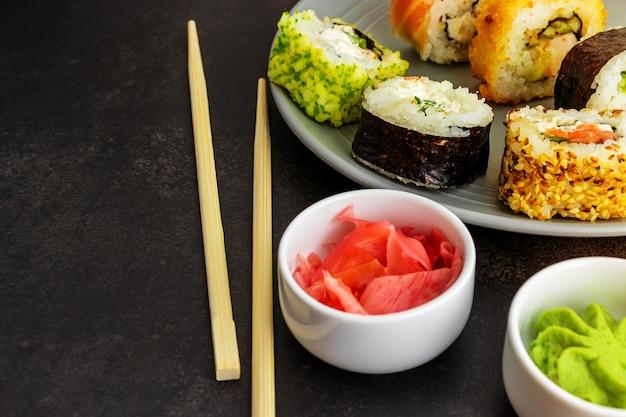 Rotoli di sushi di diversi tipi di fatti in casa in un primo piano su una superficie scura