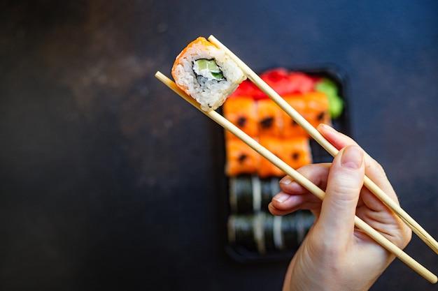 Sushi rotoli pesce salmone, verdure, riso wasabi allo zenzero e nori sul tavolo