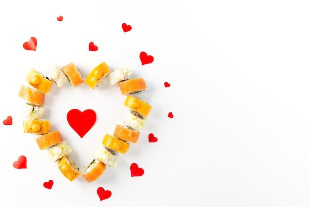 Sushi rotoli a forma di cuore su uno sfondo bianco, il giorno di san valentino.
