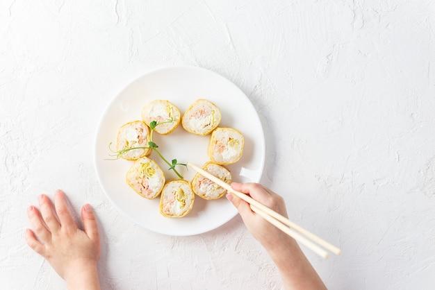 Rotoli di sushi a forma di cuore su un piatto bianco con le mani di un bambino.