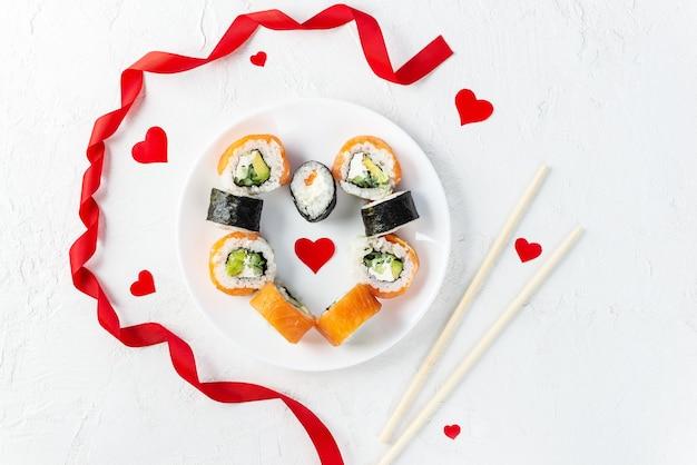 Rotoli di sushi a forma di cuore con le bacchette e un nastro rosso su un piatto bianco. san valentino.