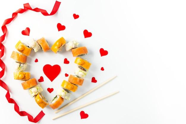 Rotoli di sushi a forma di cuore con un nastro e bacchette su uno sfondo bianco, il giorno di san valentino.