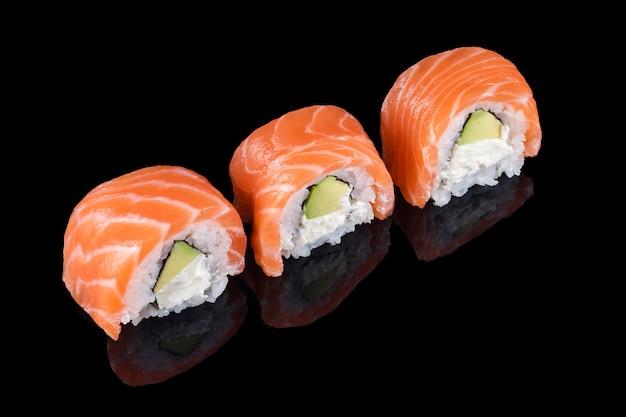 Rotoli di sushi fatti di salmone crudo fresco, crema di formaggio e avocado isolato su fondo nero con riflessi. philadelphia, sushi tradizionale con salmone, avocado e formaggio. cucina giapponese.