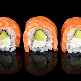 Rotoli di sushi fatti di salmone crudo fresco, crema di formaggio e avocado isolato su fondo nero con riflessi