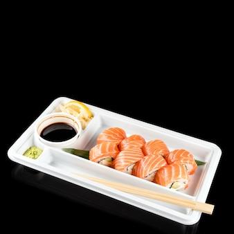 Rotoli di sushi fatti di salmone fresco crudo, crema di formaggio e avocado in un contenitore di plastica bianco pronto da mangiare su sfondo nero con riflessi