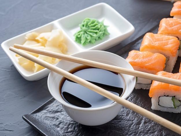 I rotoli di sushi philadelphia su un piatto nero strutturato stanno su uno sfondo grigio. bacchette wasabi zenzero e salsa. involtini con salmone, crema di formaggio, avocado.