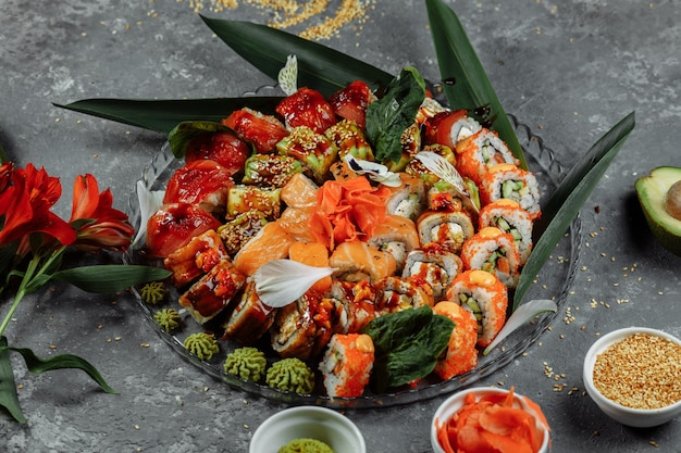 Rotoli di sushi posti su un vassoio di cristallo. rotoli: philadelphia, green dragon, hawaii, red dragon, ebi shake.