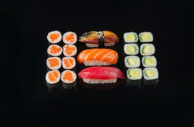 Il set di rotoli di sushi è servito su sfondo nero Foto Premium